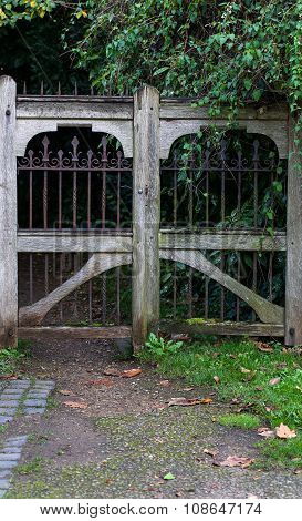 Entrance Of A Graveyard With A Closed Wooden And Wrought-iron Gate