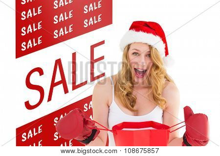 Shocked blonde opening a shopping bag with boxing gloves against sale advertisement