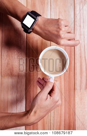 Overhead of feminine hands with smartwatch and coffee poster
