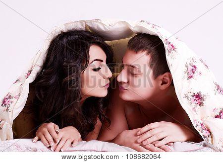 Portrait of happy loving couple under a warm blanket