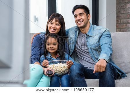 Happy young family eating popcorn while watching tv in living room