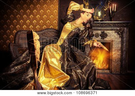 Beautiful fairy girl like a Snow White in a beautiful lush dress spins on the spinning wheel.  Renaissance. Barocco. Fashion. Fairy tale.