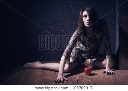 Asylum. Lonely mad woman with red apple sitting on a floor. Low key. poster