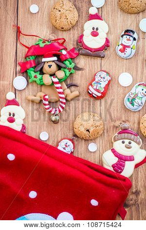 Chocolate Santas, Snowman And Biscuits Near Christmas Stocking