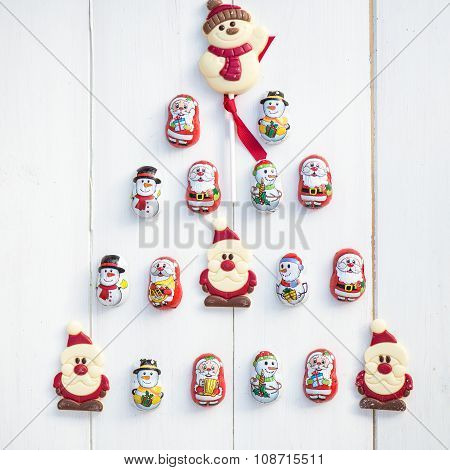 Chocolate Santas, Snowman And Biscuits Laying In A Form Of Christmas Tree
