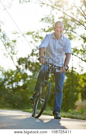 Happy man riding mountainbike in summer in nature
