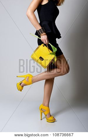 Fashion girl. Young woman posing in black dress and yellow handlbag and shoes