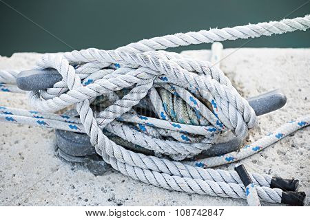 Nautical ropes tied around horn cleat on dock, close up.  Key West harbor, Florida.
