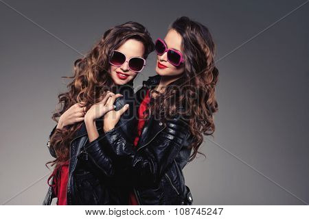 Sisters twins in hipster sun glasses laughing Two fashion models Women smiling positive Friends group having fun, talking Youthful friendship youth adults people culture concept Young women rock party poster