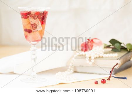 Glass Of Champagne And Cranberry Cocktail With Vintage Books And Pearls