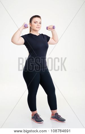 Full length portrait of a fat woman in sports wear workout with dumbbells isolated on a white background