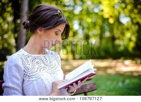 Woman Reading Book Outdoors In Peaceful Forest