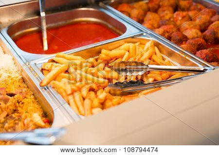 food, catering, self-service and eating concept - close up of french fries and other dishes on metallic tray