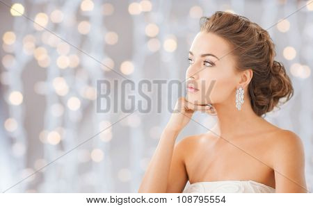 people, holidays, wedding, jewelry and luxury concept - beautiful woman wearing shiny diamond earrings over lights background