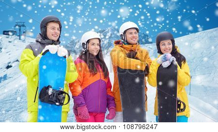 winter, leisure, extreme sport, friendship and people concept - happy friends in helmets with snowboards over snow and mountain background poster