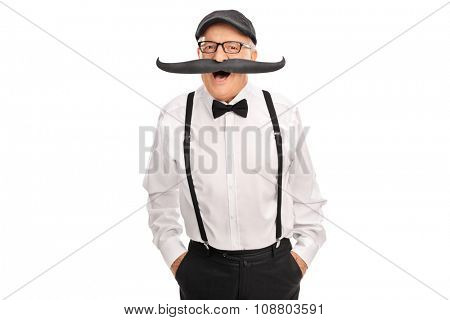 Joyful senior gentleman with a bow-tie and suspenders posing with a big fake moustache isolated on white background