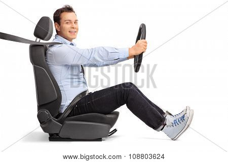 Profile shot of a young man driving seated on car seat and looking at the camera isolated on white background