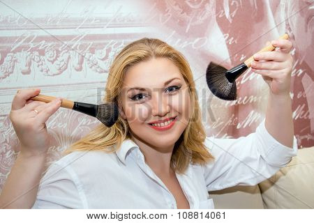 Beautiful Middle-aged Model Holding Makeup Brushes.