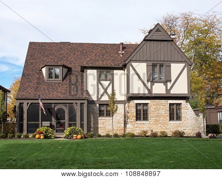 English Tudor Home with American Flag & Pumpkins