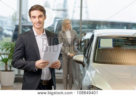 Salesman is holding papers for his client.