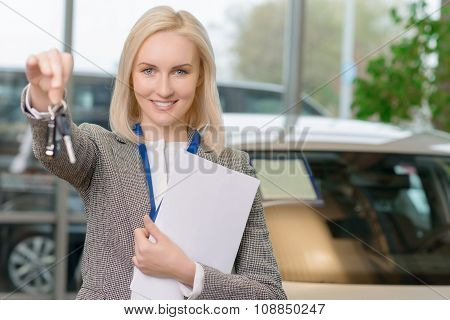 Female sales representative is upholding the car keys.