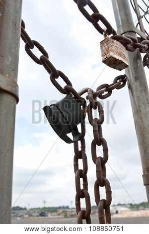 Padlocks And Chains Secure Gate To Industrial Work Site