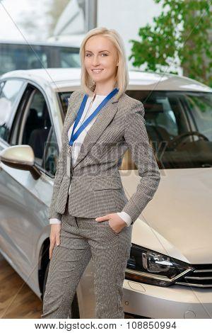 Saleswoman is posing in front of fancy car.