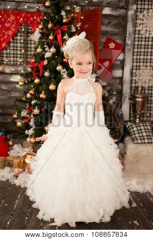 Cute Young beautiful girl in white Christmas dress. She has whit