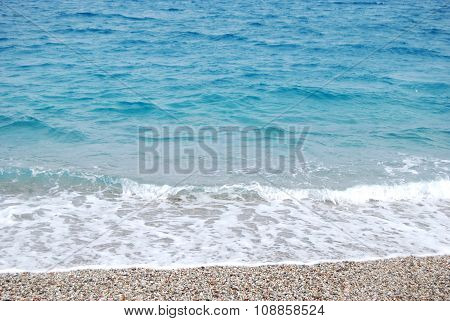 transparent deep blue wave of the sea that breaks on the shore with white foam and sand for summertime