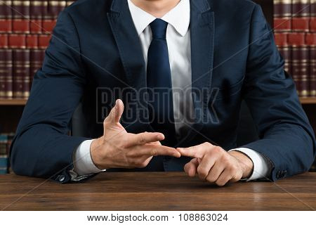 Lawyer Gesturing While Sitting At Desk