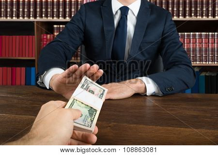 Lawyer Refusing To Take Bribe From Client At Desk
