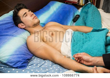 Young Man in Bed Receiving Injection