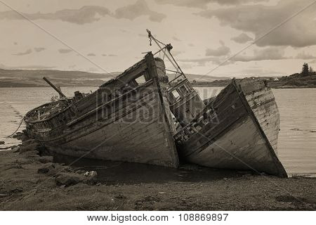 Two old wooden boats aground on isle of Mull, Scotland. Sepia.