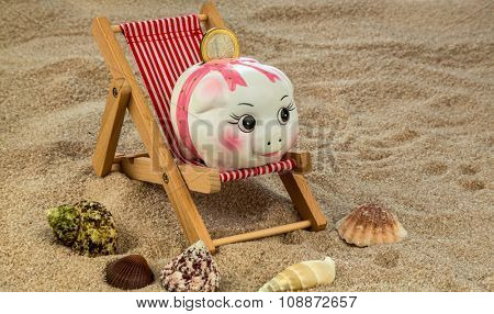 deckchair with euro currency on the sandy beach. symbol photo for costs in travel, vacation, holiday. save on vacation