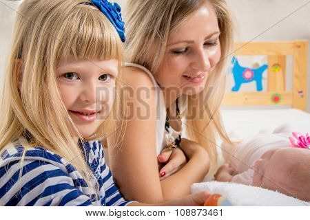 Mom Looks At A Newborn Baby, A Five-year Daughter Looking To The Frame