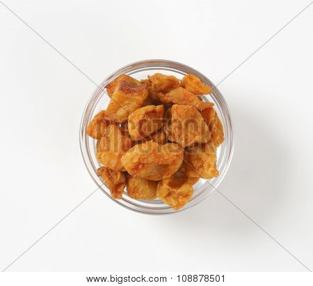 bowl of salty pork greaves on white background poster