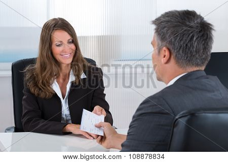 Businesswoman Giving Cheque To Businessman