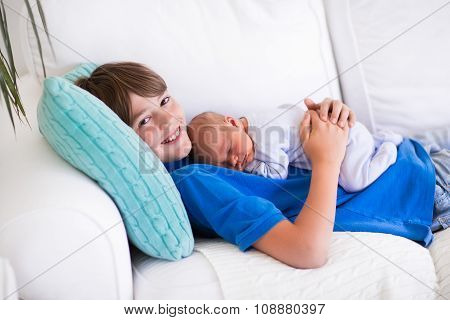 Child Holding Newborn Sibling