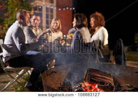 Mature Friends Enjoying Outdoor Evening Meal Around Firepit