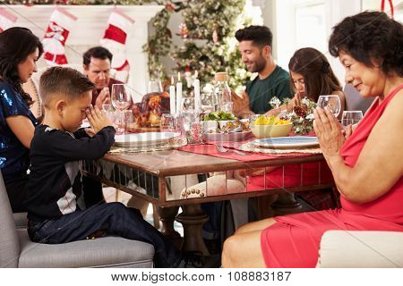 Family With Grandparents Saying Grace Before Christmas Meal