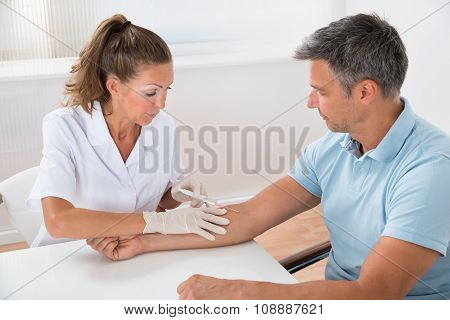 Doctor Drawing Blood From Patient With Syringe