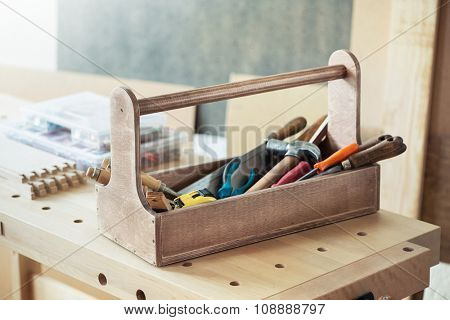Wooden toolbox with tools on workbench