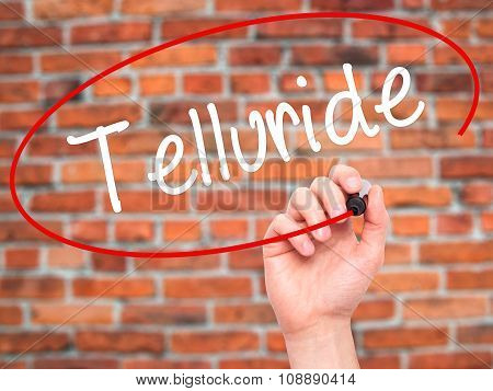 Man Hand writing Telluride with  marker on visual screen