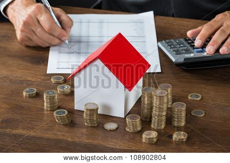 Businessman Calculating Tax By Model House And Coins