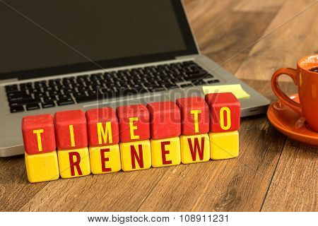 Time to Renew written on a wooden cube in a office desk