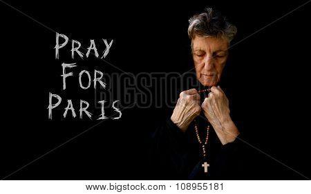 Pray For Paris. An Old Praying Woman In Black