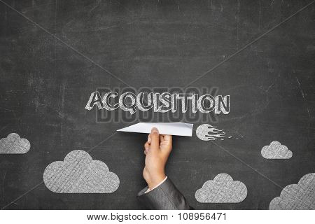 Acquisition concept on blackboard with paper plane