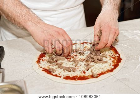 Making of a meat pizza, professional kitchen