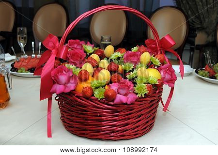 Wicker basket with blend Fruits and flowers.