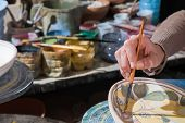 Pottery decorator from Caltagirone while finishing a ceramic tray in her work space poster